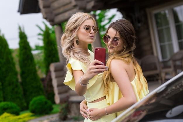 Ritratto di due damigelle d'onore piuttosto giovani in abiti gialli vicino a una casa in legno alla moda. persone concetto di stile di vita. facendo selfie sul cellulare sorridendo e inviando un bacio d'aria