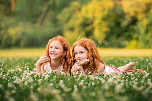 Ritratto di due ragazze felici ricci dai capelli rossi che si trovano tra i fiori di trifoglio bianco white