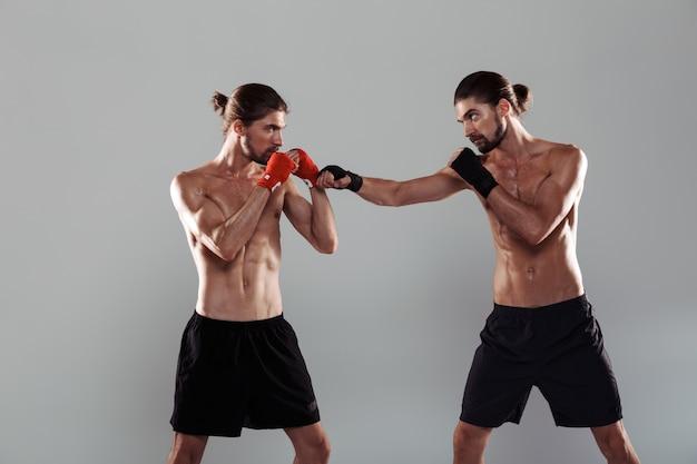 Ritratto di due fratelli gemelli a torso nudo muscolosi seri