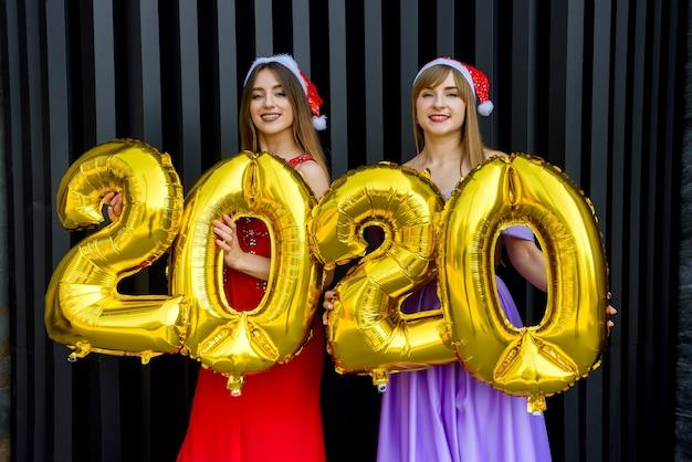 Ritratto di due ragazze sorridenti felici in abiti natalizi in posa con palloncini numerici color oro 2020