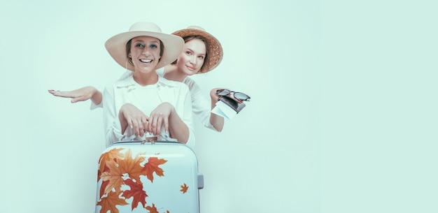 Ritratto di due donne sorridenti con passaporti, carte d'imbarco e una valigia. concetto di viaggio. tecnica mista