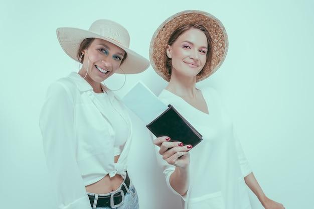 Ritratto di due donne sorridenti con passaporti e carte d'imbarco nelle loro mani. concetto di viaggio. tecnica mista