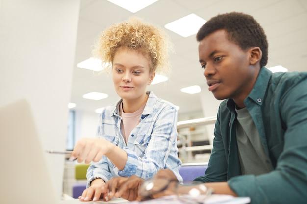Ritratto di due studenti, ragazza caucasica e ragazzo africano, che punta allo schermo del laptop durante il lavoro