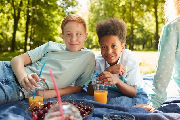 Ritratto di due ragazzi adolescenti mentre vi godete un picnic con gli amici nel parco all'aperto