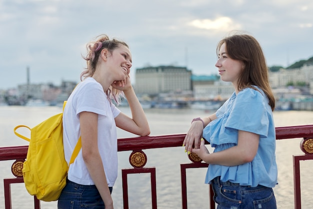 Ritratto di due amici di ragazze adolescenti che camminano e parlano sul ponte pedonale il giorno di estate soleggiato. amicizia, stile di vita, gioventù, adolescenti