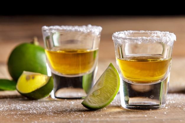 Ritratto di due colpi di tequila con fetta di lime e sale sulla tavola di legno