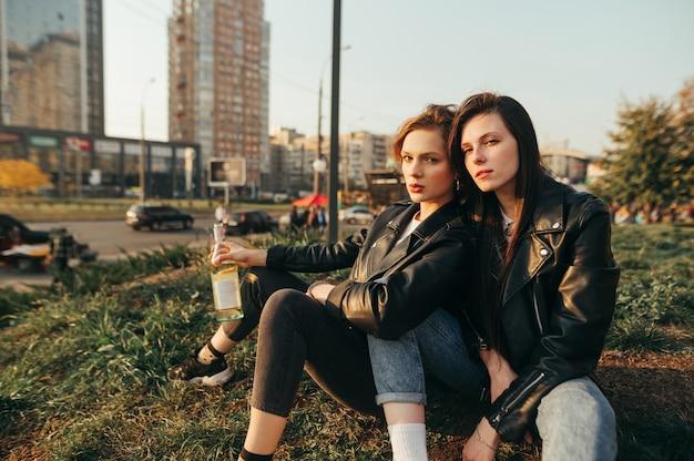 Ritratto di due amiche alla moda seduti la sera per terra con una bottiglia di vino in mano