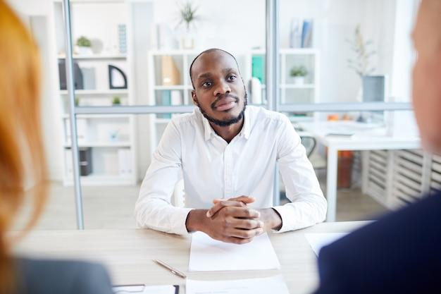 Ritratto di due uomini d'affari irriconoscibili intervistando uomo afro-americano per posizione di lavoro in ufficio, copia spazio
