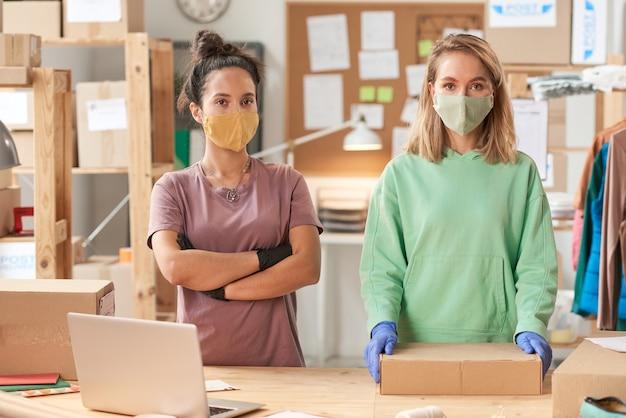 Ritratto di due donne in maschere guardando davanti a lavorare nel servizio di consegna