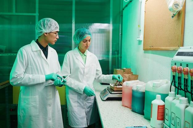 Ritratto di due lavoratori che indossano indumenti protettivi che lavorano nel laboratorio bio illuminato da luce verde, copia dello spazio
