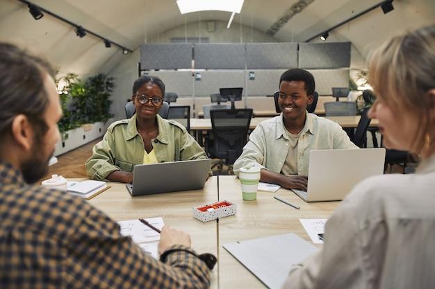 Ritratto di due giovani afro-americani sorridenti a partner commerciali seduti sul tavolo durante la riunione in un ufficio moderno, copia dello spazio