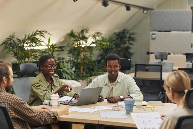 Ritratto di due giovani afro-americani sorridenti ai colleghi seduti a tavola durante la riunione in un ufficio moderno e discutendo del progetto di lavoro, spazio di copia