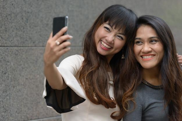 Ritratto di due giovani donne d'affari asiatiche insieme nella città all'aperto