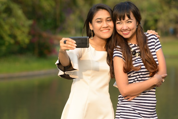Ritratto di due giovani donne asiatiche insieme rilassante al parco all'aperto