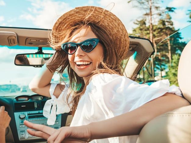 Ritratto di due giovani belle e sorridenti ragazze hipster in auto decappottabile