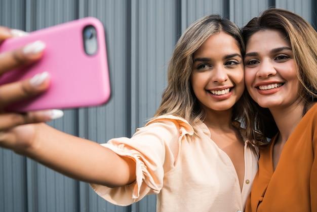 Ritratto di due giovani amici divertendosi insieme e prendendo un selfie con un telefono cellulare all'aperto. concetto urbano.