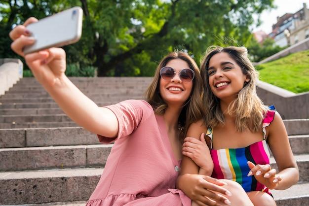 Ritratto di due giovani amici sorridenti e prendendo un selfie con il proprio telefono cellulare mentre è seduto all'aperto. concetto urbano.