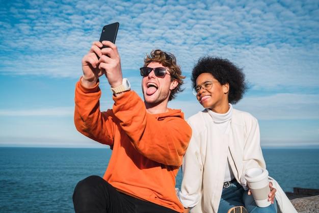 Ritratto di due giovani amici che trascorrono del buon tempo insieme e prendendo un selfie con lo smartphone all'aperto sul mare.