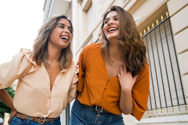 Ritratto di due giovani amici che trascorrono del buon tempo insieme mentre si cammina all'aperto. concetto urbano.