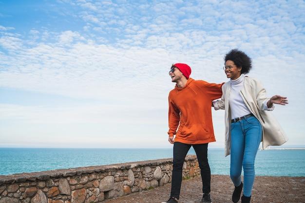 Ritratto di due giovani amici che trascorrono del tempo piacevole insieme, camminando sulla linea di costa e divertendosi.