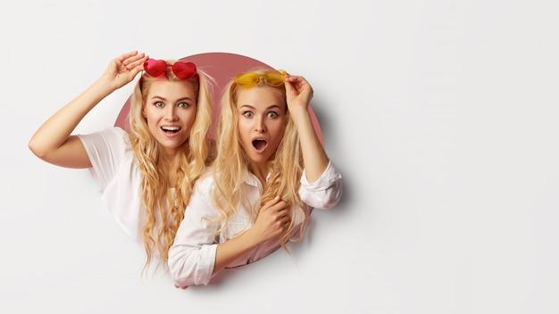 Ritratto di due giovani donne felici, scioccate negli occhiali da sole a forma di cuore che guardano attraverso il buco bianco nel muro. grande vendita. facce buffe. spazio vuoto per il testo
