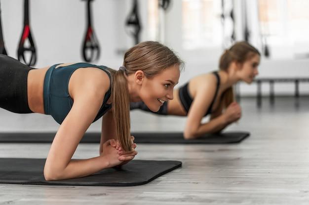 Ritratto di due giovani ragazze sportive che fanno tavola con cinghie fitness trx in palestra