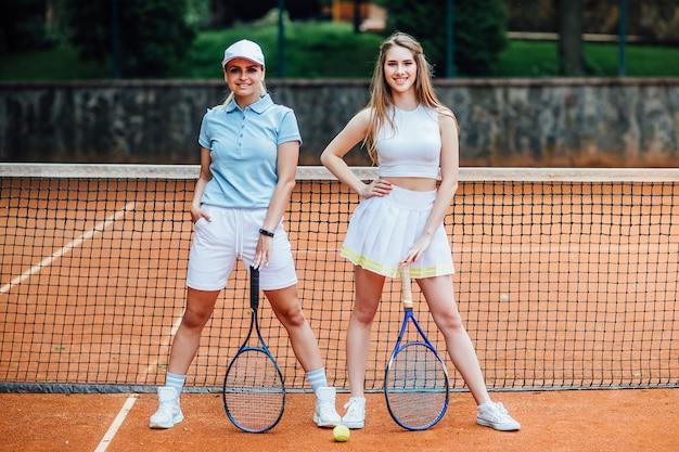 Ritratto di due giovani donna pronta per giocare nel campo da tennis con racchette all'aperto.
