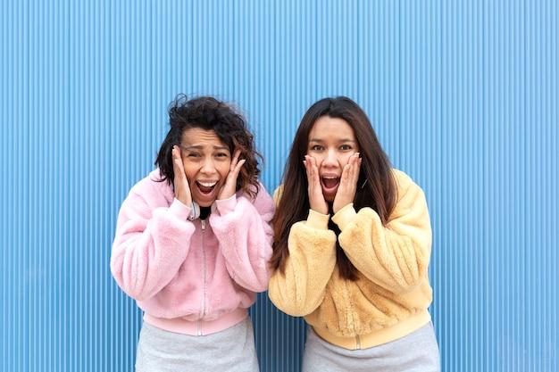Ritratto di due giovani donne su sfondo blu hanno le mani sui loro volti e urlano di paura. concetto di terrore, sorpresa o panico. spazio per il testo.