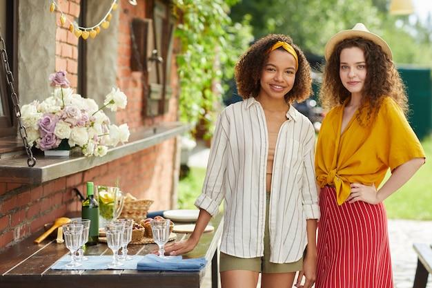Ritratto di due giovani donne vestite di colorati abiti estivi in posa sulla terrazza all'aperto durante la cena con gli amici