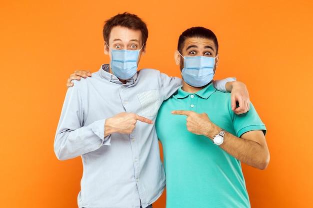 Ritratto di due giovani lavoratori con maschera medica chirurgica in piedi, abbracciati, mostrati e puntati l'un l'altro e guardando la telecamera con una faccia buffa. colpo dello studio dell'interno isolato su priorità bassa arancione.