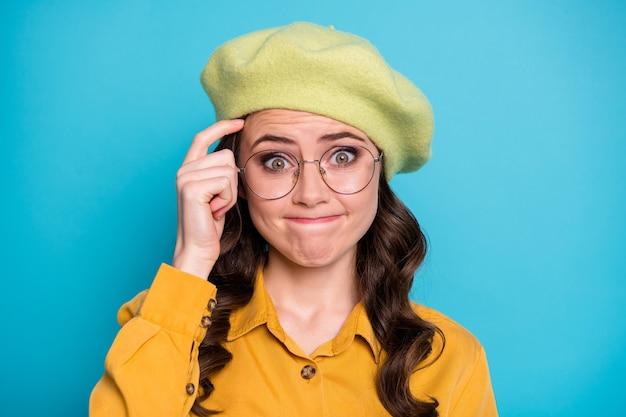 Il ritratto di una ragazza ignorante inconsapevole ha una domanda difficile che non riesce a trovare risposta graffiare la fronte del dito indossare un bell'abito isolato su uno sfondo di colore blu