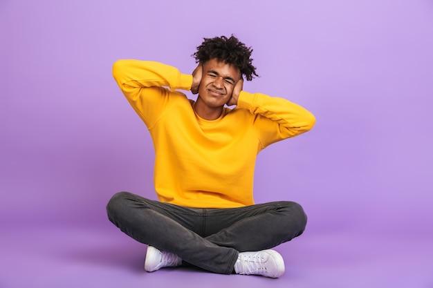 Ritratto di infelice ragazzo afroamericano seduto sul pavimento con le gambe incrociate e coprendo le orecchie con le mani, isolato su sfondo viola violet