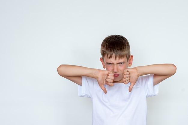 Ritratto del bambino infelice, arrabbiato, dispiaciuto che dà i pollici giù il gesto della mano