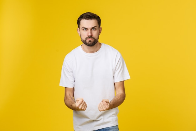 Uomo bello infelice del ritratto che guarda l'obbiettivo su spazio giallo