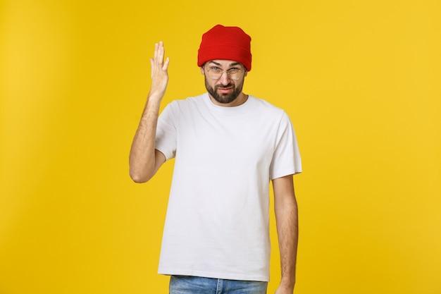 Uomo bello infelice del ritratto che guarda l'obbiettivo su giallo.