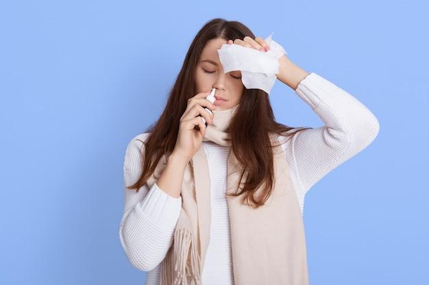 Ritratto di giovane donna infelice che tiene il tovagliolo e usando lo spray nasale, toccandosi la testa, soffre di mal di testa e febbre, tiene gli occhi chiusi, indossa un maglione bianco e sciarpa.