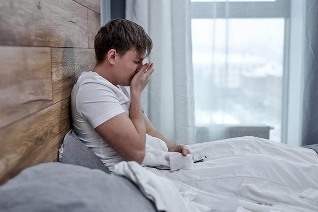 Ritratto di uomo malsano che sente dolore alla gola e febbre alta, seduto sul letto da solo. coronavirus e covid-19. concetto di mal di testa, malattia, influenza, medicina e sanità