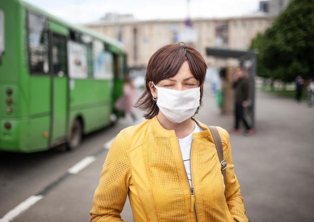 Ritratto di una donna di mezza età non identificata in maschera bianca e abiti casual in posa a una fermata dell'autobus in attesa del trasporto pubblico
