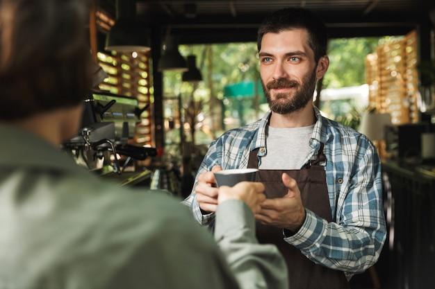 Ritratto di un barista non rasato che indossa un grembiule che sorride mentre lavora in un caffè di strada o in un caffè all'aperto