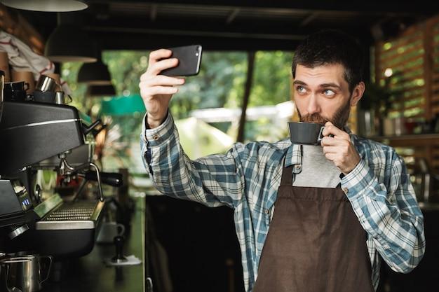 Ritratto di barista non rasato uomo che indossa un grembiule che prende selfie foto con una tazza di caffè mentre si lavora in street cafe o coffeehouse all'aperto