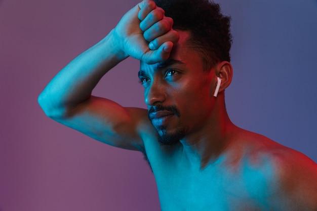 Ritratto di un uomo afroamericano senza camicia senza barba che posa con un auricolare isolato su un muro viola