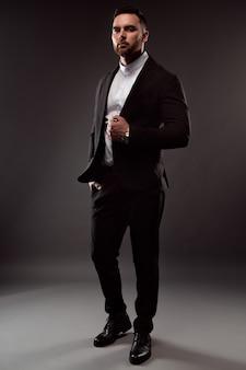 Ritratto di un uomo d'affari con la barba lunga vestito con un abito nero e una camicia bianca