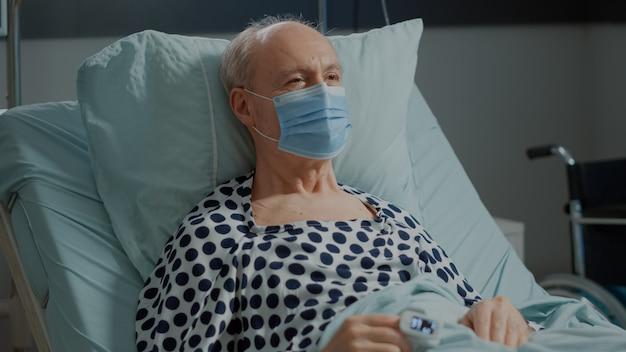 Ritratto di paziente malato nel letto del reparto ospedaliero seduto con ossimetro e maschera facciale in auto intensiva...