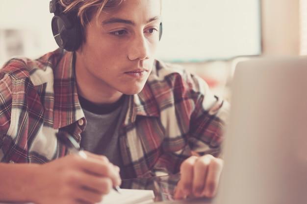 Ritratto di adolescente caucasico con le cuffie che fissa lo schermo del laptop durante la riproduzione di giochi per computer, chat su internet o la visualizzazione di video. - immagine