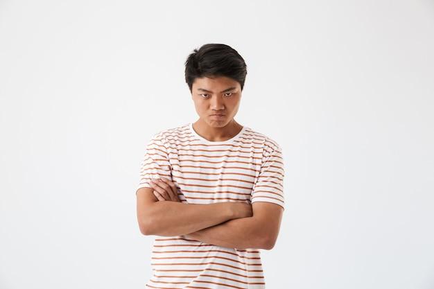 Ritratto di un uomo asiatico sconvolto in piedi con le braccia conserte
