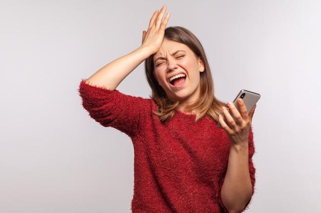 Ritratto di donna depressa sconvolta in piedi con gesto facepalm e tenendo il telefono cellulare