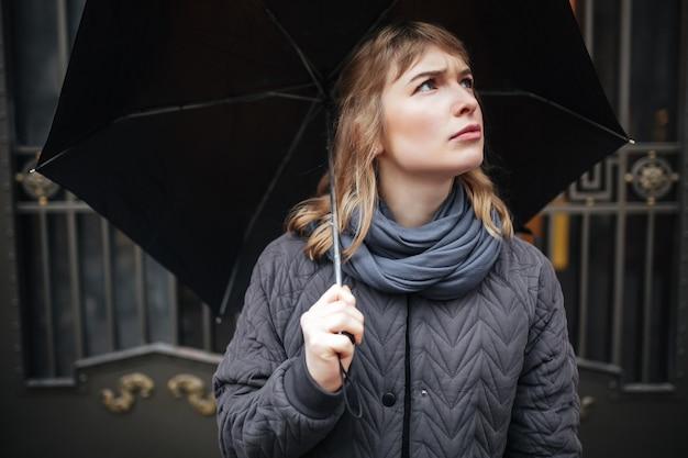 Ritratto di signora sconvolta in piedi sulla strada con ombrello nero e tristemente alzando lo sguardo