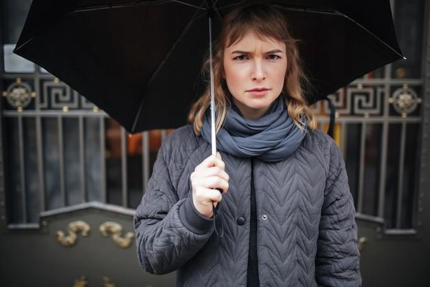 Ritratto di signora sconvolta in piedi sulla strada con ombrello nero e purtroppo