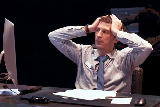 Ritratto di impiegato sconvolto, manager uomo seduto davanti al monitor del computer.