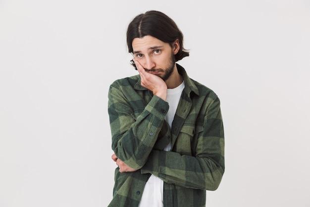 Ritratto di un giovane uomo barbuto sconvolto che indossa abiti casual in piedi isolato sul muro